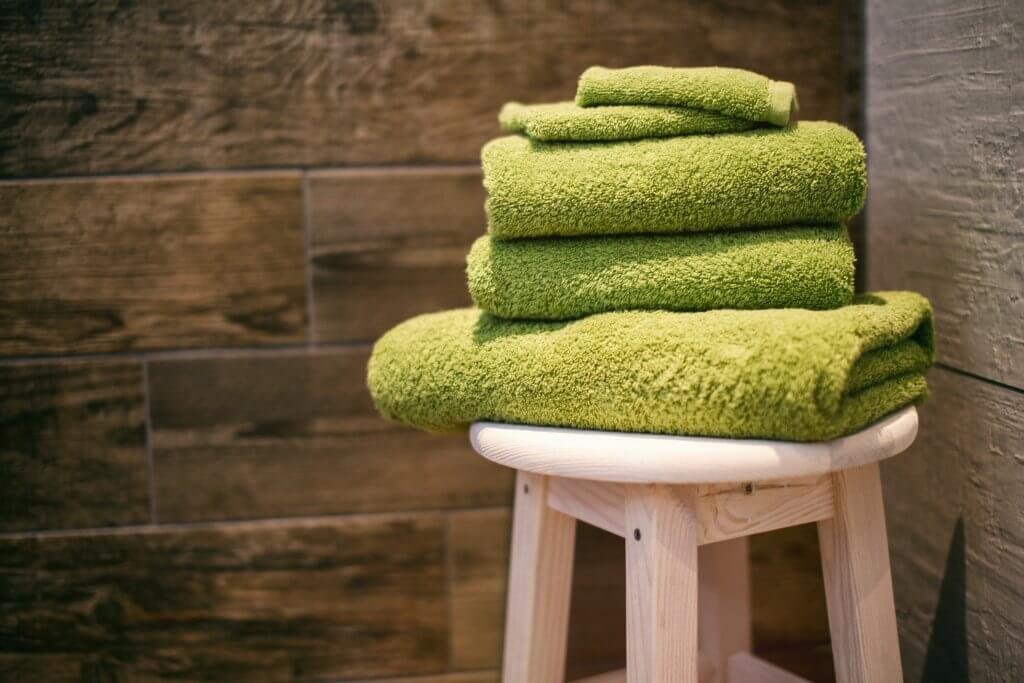 Stack of green towels on a stool.