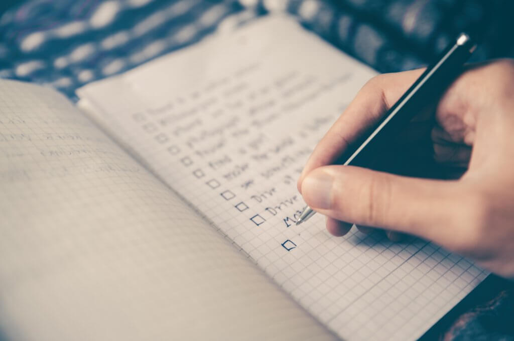 Person writing a checklist. Photo by Glenn Carstens-Peters on Unsplash