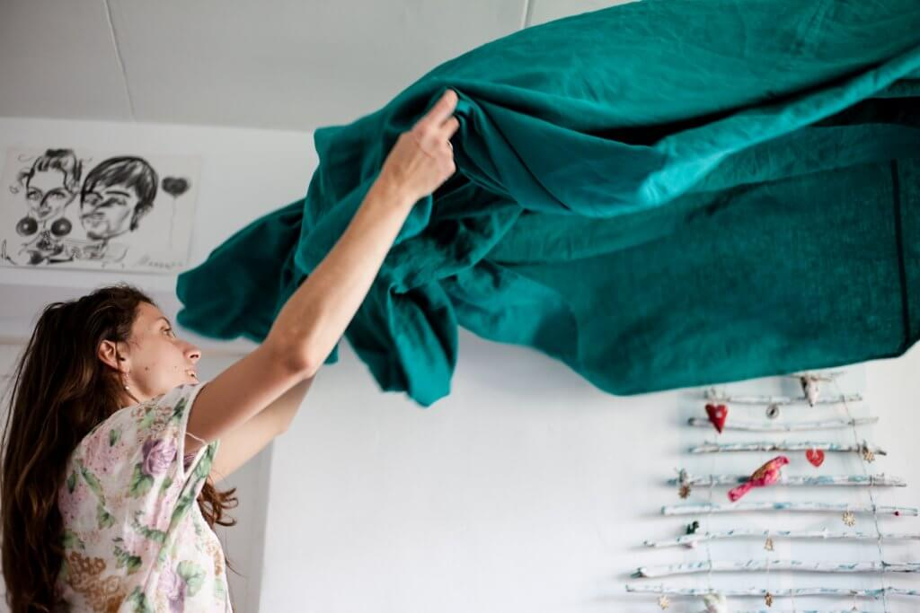 Woman lifting blanket. Photo by Volha Flaxeco on Unsplash.