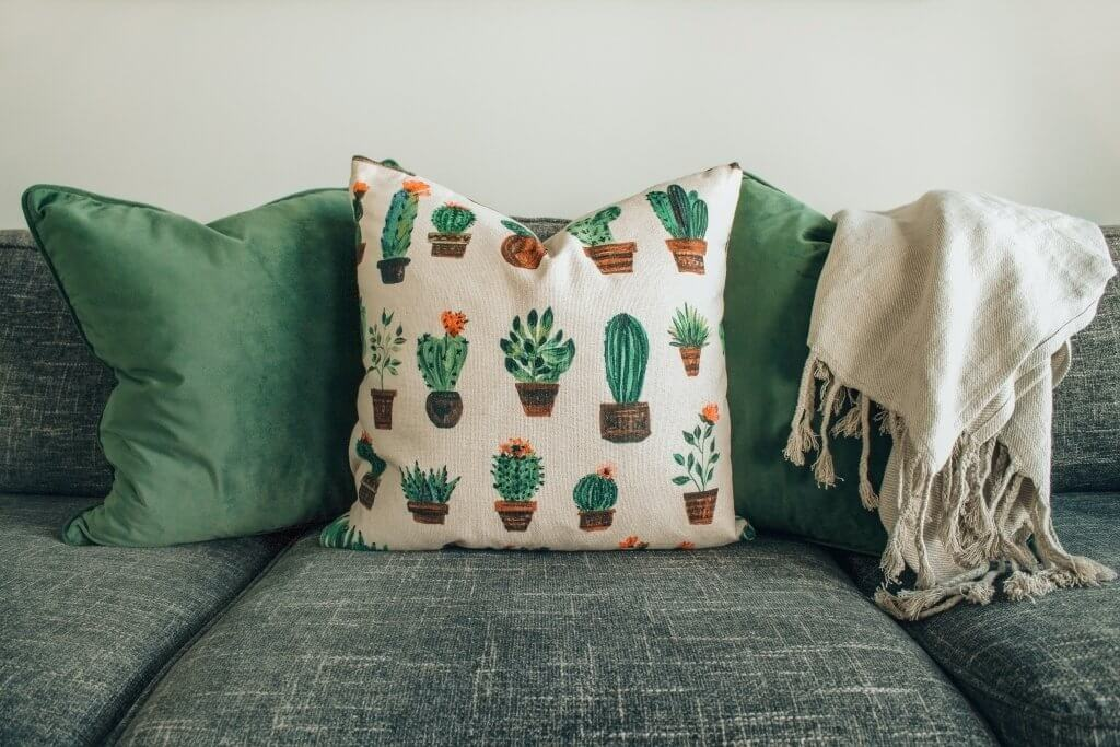 Couch with pillows and linens. Photo by DESIGNECOLOGIST on Unsplash.