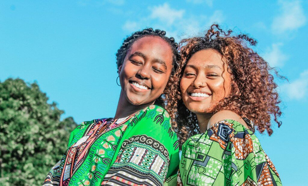 Two woman smiling. Photo by Kirschner Amao on Unsplash.